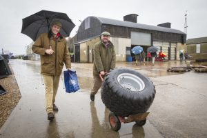Two farmers pleased with their purchase of a trailer wheel.
